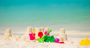 Sandcastle at white beach with plastic kids toys Royalty Free Stock Photo