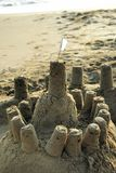 Sandcastle with a White Flag. A small sandcastle with a white flag on beach Stock Photo