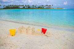 Sandcastle at white tropical beach with plastic Royalty Free Stock Photography