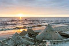 Sandcastles построенные на пляже морем с заходом солнца в bac Стоковые Изображения RF