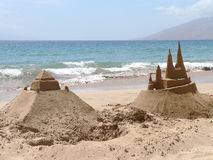 Sandcastles. Two sandcastles built by a tourist family await the fate of high tide on a southern beach in Maui, Hawaii Royalty Free Stock Image