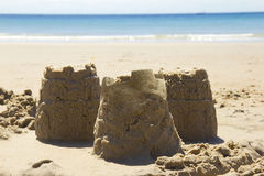 Sandcastles and beach. Three sandcastles with blue sea in background Royalty Free Stock Images