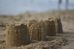 Sandcastles on a beach. Four sandcastles lie in the shore with waves lapping in the background Royalty Free Stock Images