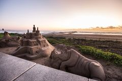 Sandcastles on a beach at sunrise. Sandcastles and sand sculpture of a rhino on a beach in Durban, South Afirca with a pier in the background at sunrise Royalty Free Stock Images