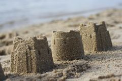 Sandcastles on a beach. Three sandcastles lie on the shore with waves lapping in the background Royalty Free Stock Image