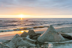Sandcastles built on the beach by the sea with sunset in the bac Royalty Free Stock Images
