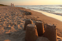 Sandcastles with Couple and Dog in Background Royalty Free Stock Images