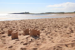 Sandcastles and Dunstanburgh Castle. Slowly dissolving sandcastles with dunstanburgh in Background Royalty Free Stock Images