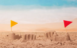 Sandcastles with flags on the background of sea. Royalty Free Stock Photos
