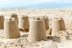 Sandcastles on the sand of a beach. Closeup of several sandcastles on the sand of a beach, with the sea in the background Royalty Free Stock Photography