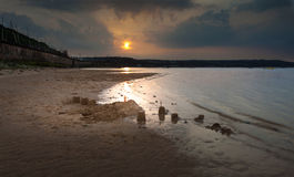 Sandcastles at sunset. Sandcastles being washed away at a little strip of sand on Swansea Bay that's rarely exposed, near Mumbles, Swansea Royalty Free Stock Image