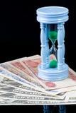 Sandclock en billete de banco representa el dinero crece en un cierto plazo Foto de archivo libre de regalías