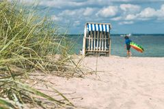Sanddüne mit Gras und das gefärbte Blau überdachten Stühle auf sandigem Strand und verwischten Kinder im Hintergrund Travemunde d Stockfotografie
