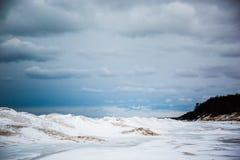 Sanddünen und gefrorene Wellen am bewölkten Tag lizenzfreies stockbild