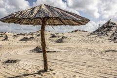 Sanddünen und Strohregenschirm allein lizenzfreie stockfotos
