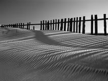 Sanddyn mot staket Arkivfoto