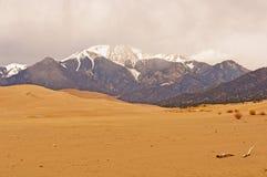 Sanddyn och snö på bergen Arkivfoto