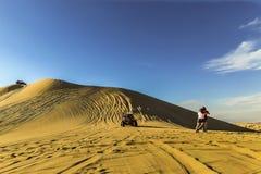 Sanddynbarnvagn som springer ner lutningen som turister som åt sidan flyttar sig fotografering för bildbyråer