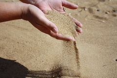Sanden flödar ner från gömma i handflatan Arkivbild