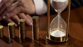 Sandglass和堆在桌,存户在储款的收入兴趣上的硬币 免版税库存图片
