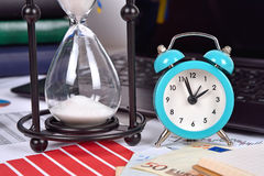 Sandglass and alarm clock Stock Images