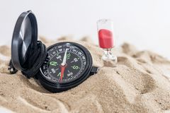 Sandglass, dollar and compass on sand isolated on white. Summer concept stock photo