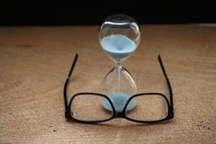 Sandglass, glasses. Time running out, sandglass, glasses Royalty Free Stock Images