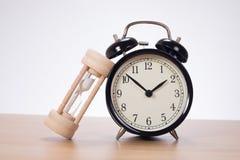 Sandglass leaning against alarm clock Stock Image