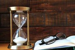 Sandglass med boken och glasögon Royaltyfri Fotografi