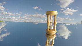 Sandglass on mirror and clouds motion, Time concept, timelapse, 4K
