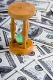 Sandglass on a stack of dollars Stock Photography