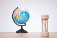 Sandglass z kulą ziemską na prostym tle zdjęcia stock