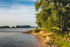 Sandig bank av en bred holländsk flod med en vågbrytare Arkivbilder