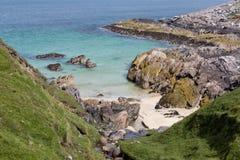 Sandig fjärd på den steniga stranden Royaltyfria Foton