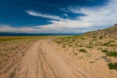 Sandig gropig väg längs kusten av sjön Sommarnatursikt Arkivfoto
