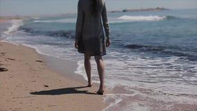 Sandig kust med skummande vågor Tillbaka nära sikt av en härlig barfota flicka i en kort klänning som promenerar det sandigt lager videofilmer