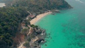Sandig kustlinje med gröna skogar och bruna byggande tak arkivfilmer