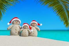 Sandig snögubbefamilj för jul i jultomtenhattar på Palm Beach royaltyfri fotografi