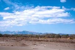 Sandig strand, berg och blå himmel royaltyfri foto