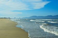 Sandig strand, blått hav med skum för vitt hav och berg på bakgrund för blå himmel Royaltyfri Fotografi