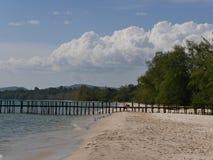 Sandig strand, brygga och hav Arkivfoto