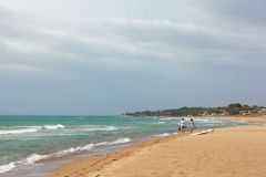 Sandig strand för sommarhavssikt, vågor i solig dag Moussera vågor som sveper på stranden Två tonåringar promenerar kusten royaltyfria foton