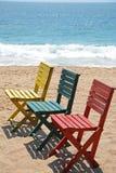 Sandig strand för tre färgglade trästolar Arkivbilder
