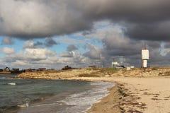 Sandig strand Grå färgmoln Vit fyr Arkivbilder