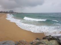 Sandig strand i regnet royaltyfria foton