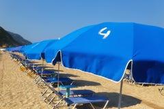 Sandig strand med blåa slags solskydd och sunbeds Arkivbild
