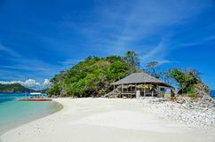Sandig strand med bungalower och ett fartyg nära ön av Busuanga Royaltyfri Foto