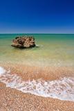 Sandig strand med en stor sten Royaltyfri Foto
