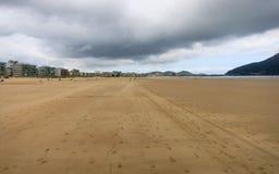 Sandig strand med fotspår och hus i bakgrunden Arkivbild
