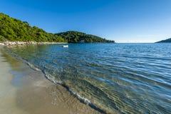 Sandig strand med klara vattenvågor Arkivfoton
